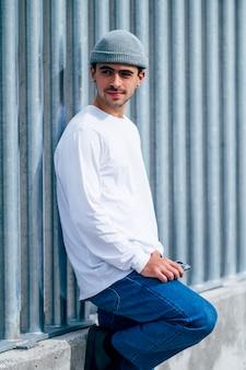 Mężczyzna pozuje kapelusz, dżinsy i białą koszulkę