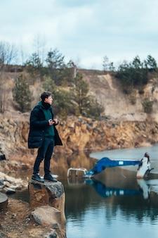Mężczyzna pozuje w kamieniołomie w pobliżu rzeki