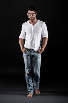 Mężczyzna pozuje z okularami, dżinsami i białą koszulką