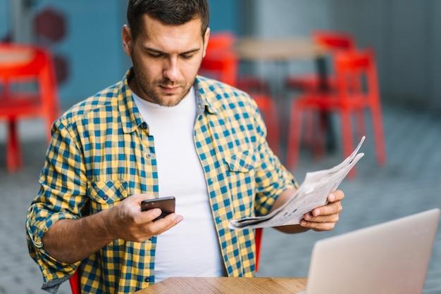 Mężczyzna pozuje z telefonem i gazetą