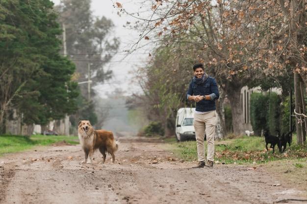 Mężczyzna pozycja i jego pies pozycja na drodze polnej