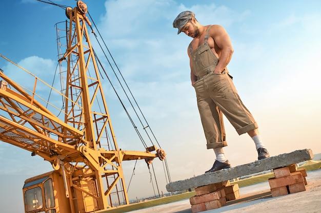 Mężczyzna pozycja na betonowej budowie na wysokości.