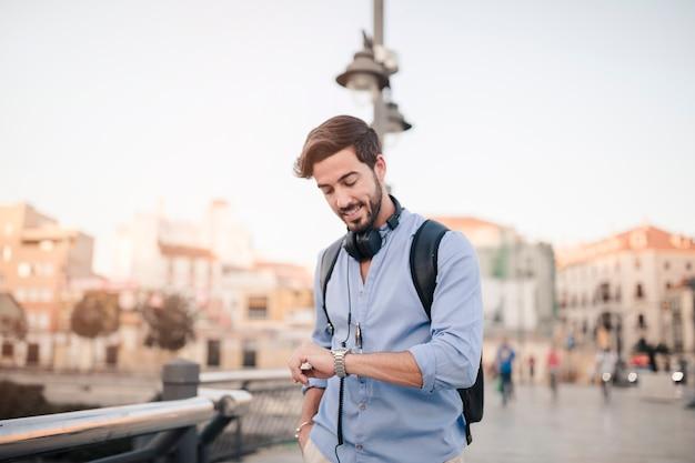 Mężczyzna pozycja przed miasto budynkiem patrzeje czas na zegarku