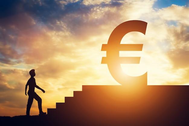 Mężczyzna pozycja przed schodkami z euro znakiem na wierzchołku