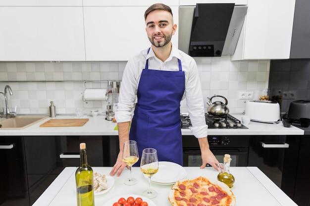 Mężczyzna pozycja przy stołem z pizzy i wina szkłami