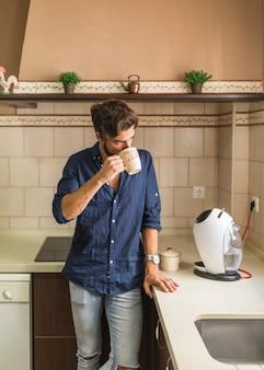 Mężczyzna pozycja w kuchni pije kawę