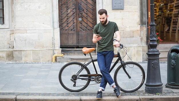 Mężczyzna pozycja z jego bicyklem używać smartphone