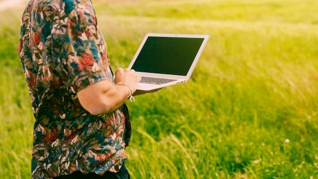 Mężczyzna pozycja z laptopem w polanie