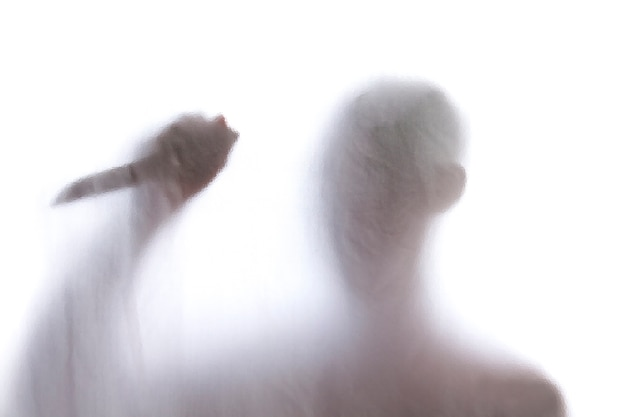 Mężczyzna pozycja za oszronionym szkłem i trzymać nóż