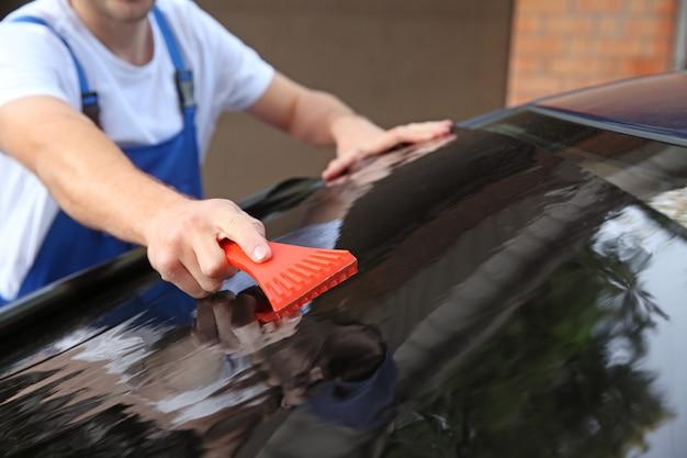 Mężczyzna pracownik barwienia szyby samochodu na zewnątrz
