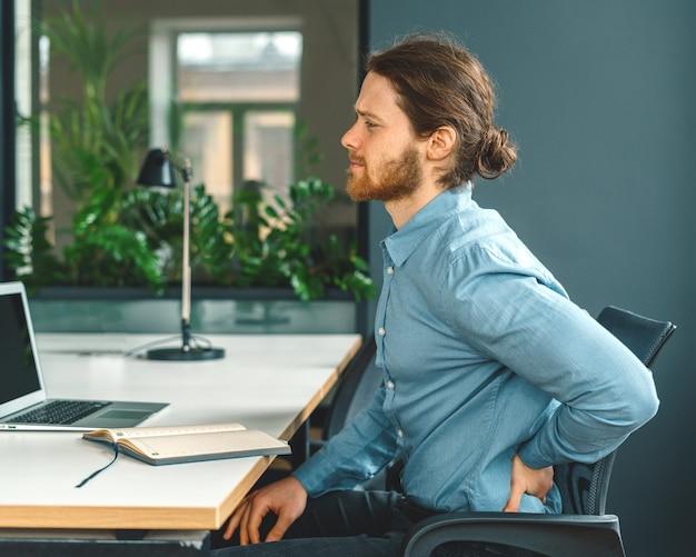 Mężczyzna pracownik biurowy cierpiący na straszny ból w dolnej części pleców