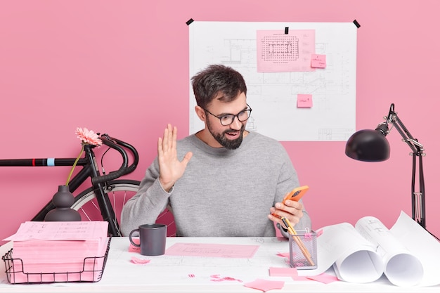 Mężczyzna pracownik biurowy prowadzi rozmowy wideo z kolegami pozuje na pulpicie, pracuje nad pozami projektu domu w przestrzeni coworkingowej