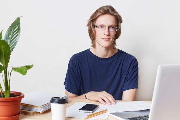 Mężczyzna pracownik biurowy w modnej fryzurze, nosi okulary i koszulkę, siedzi przy stole, pracuje z dokumentami