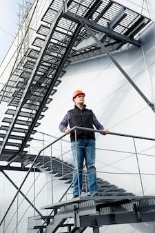 Mężczyzna pracownik budowlany stojący na stalowych schodach w fabryce