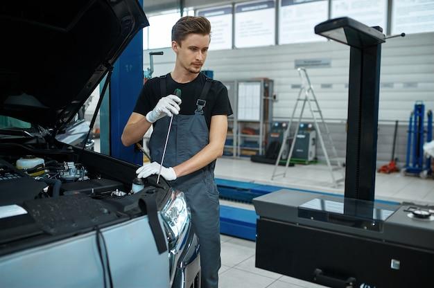 Mężczyzna pracownik dostosowuje reflektory w warsztacie mechanicznym