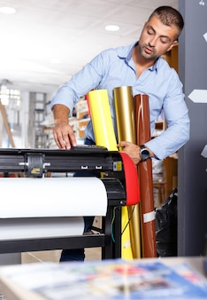 Mężczyzna pracownik drukarski z rolkami kolorowego papieru