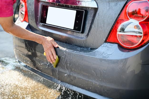 Mężczyzna pracownik myjący i pocierający gąbką na tylnym samochodzie
