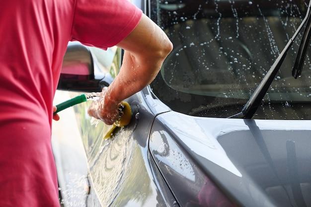 Mężczyzna pracownik myjący i pocierający samochód gąbką i wodą