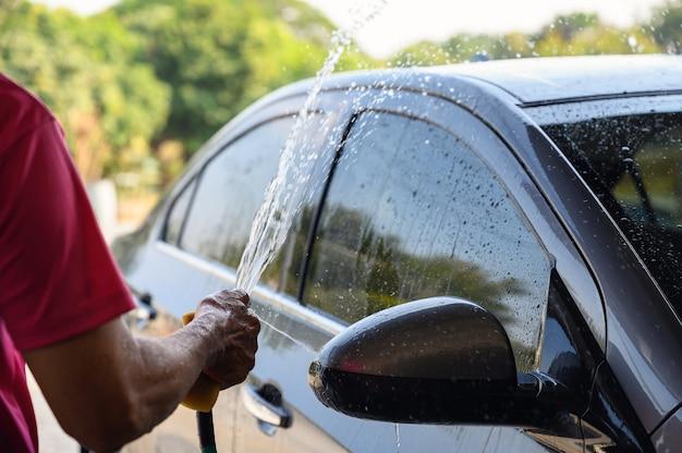 Mężczyzna pracownik myjący i spryskujący wodą samochód