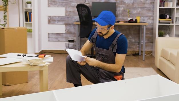 Mężczyzna pracownik nosi okulary ochronne przed montażem mebli w mieszkaniu. pracownik w sprzęcie ochronnym