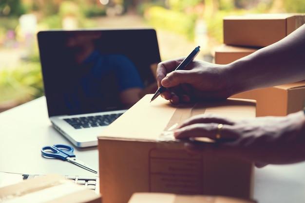 Mężczyzna pracownik pisząc adres klienta dostarczyć przesyłki sprzedaży online. właściciel małej firmy przesyłka sprzedaż online