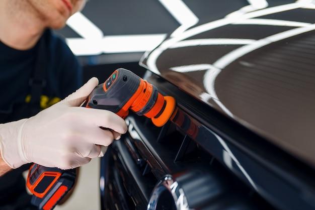 Mężczyzna pracownik poleruje kratkę chłodnicy za pomocą maszyny do polerowania, zbliżenie szczegółowości samochodu. przygotowanie przed montażem powłoki chroniącej lakier samochodu przed zarysowaniami, auto tuning