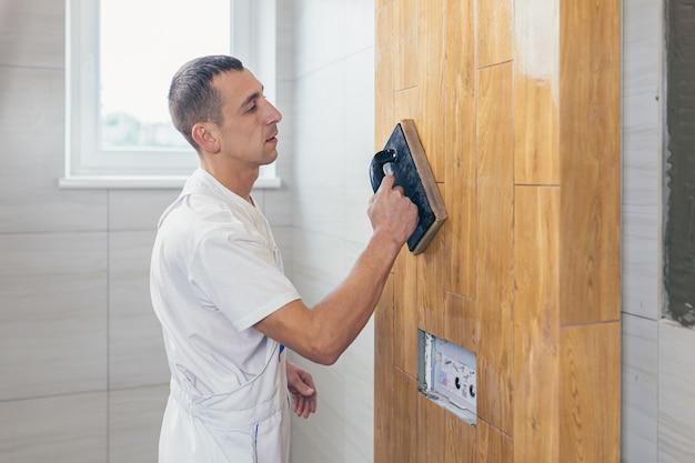 Mężczyzna pracownik profesjonalny mistrz układania płytek ceramicznych na ścianie