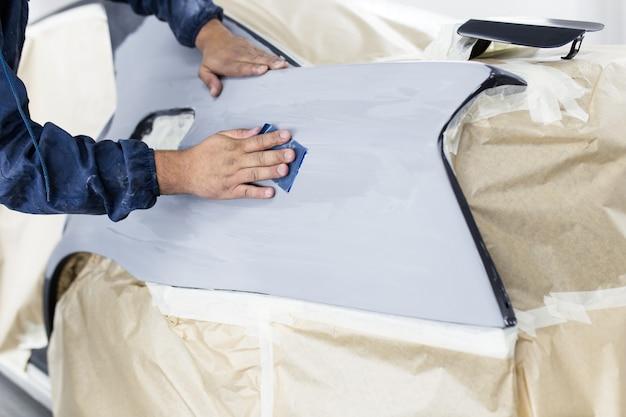 Mężczyzna pracownik przygotowuje samochód do malowania. selektywne skupienie.