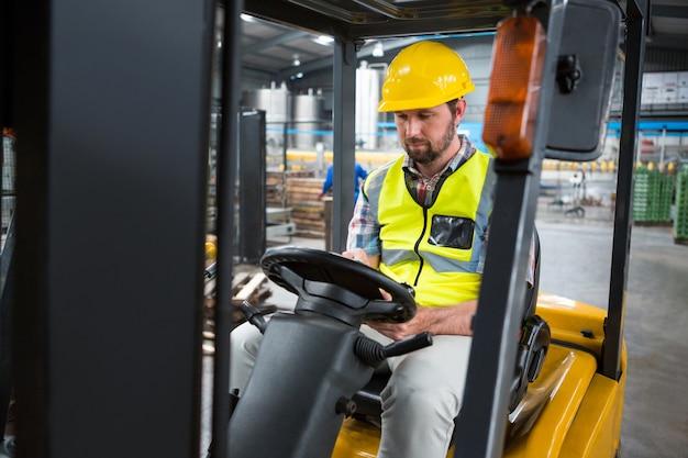 Mężczyzna pracownik siedzi w wózku widłowym