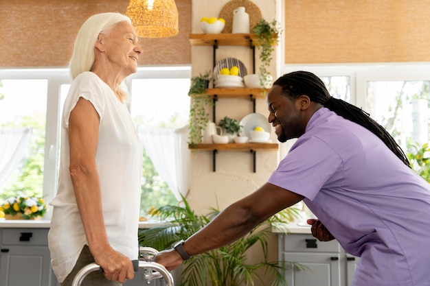 Mężczyzna pracownik socjalny opiekujący się starszą kobietą