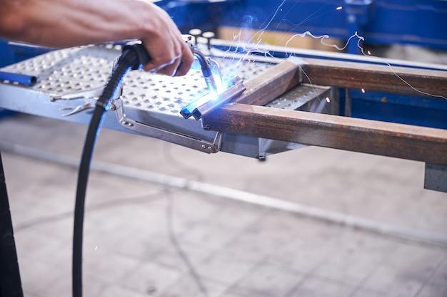Mężczyzna pracownik spawanie metalowych narzędzi w garażu