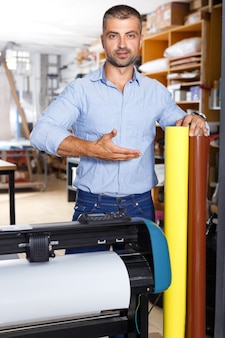 Mężczyzna pracownik studia reklamowego z rolkami kolorowego papieru stojący przy drukarce