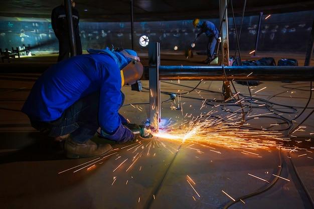 Mężczyzna pracownik szlifowania na stalowej płycie z błyskiem iskier z bliska nosić rękawice ochronne olej w zamkniętych przestrzeniach.
