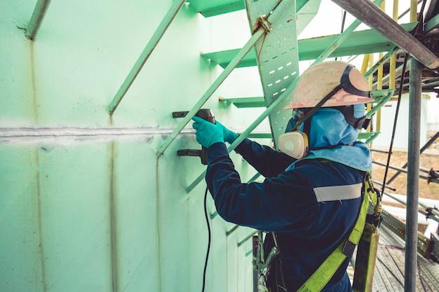 Mężczyzna pracownik testowy stalowy zbiornik spoina doczołowa powłoka węglowa płyta zbiornika magazynowego tło oleju biały kontrast pola magnetycznego test praca na wysokości pełna uprząż