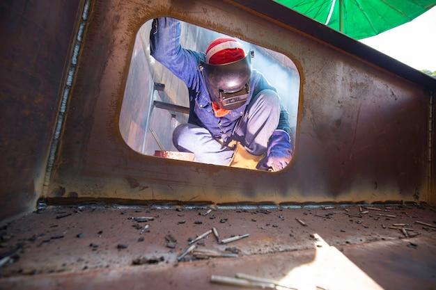 Mężczyzna pracownik ubrany w odzież ochronną i naprawa pontonowego włazu spawanie dymu przemysłowego zbiornika magazynowego pływaka oleju w zamkniętych przestrzeniach.