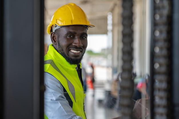 Mężczyzna pracownik w kamizelce bezpieczeństwa i kasku podczas prowadzenia wózka widłowego