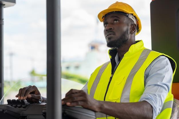 Mężczyzna pracownik w kamizelce odblaskowej i żółtym kasku jazdy wózkiem widłowym w fabryce magazynu