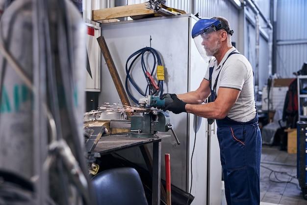Mężczyzna pracownik w masce ochronnej używający szlifierki w garażu