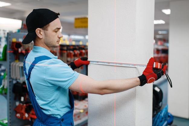 Mężczyzna pracownik w mundurze testująca taśma pomiarowa w sklepie narzędziowym