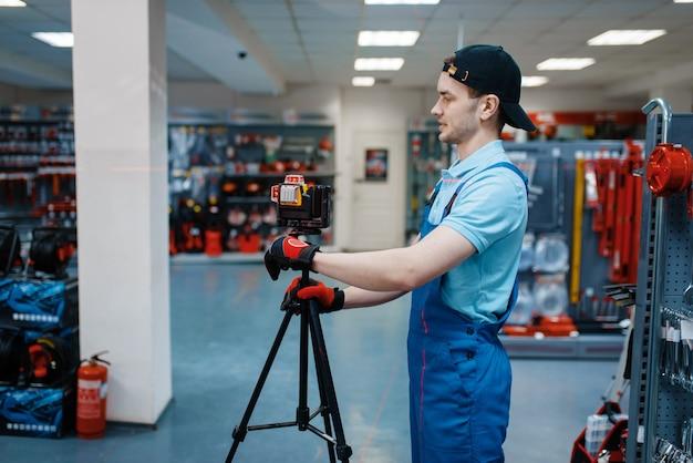 Mężczyzna pracownik w mundurze testującym poziom lasera na statywie w sklepie narzędziowym