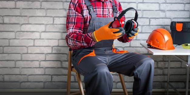 Mężczyzna pracownik w mundurze zakładanie słuchawek ochronnych. bezpieczeństwo budowy. transparent.