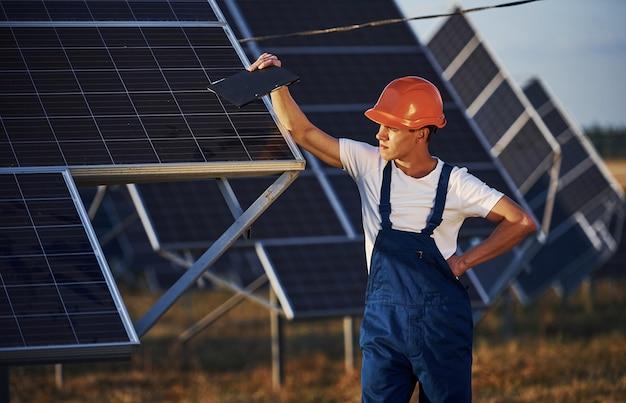 Mężczyzna pracownik w niebieskim mundurze na zewnątrz z bateriami słonecznymi w słoneczny dzień.
