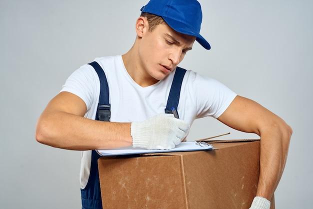 Mężczyzna pracownik z pudełkiem w rękach dostawy usługi załadunku pakowania