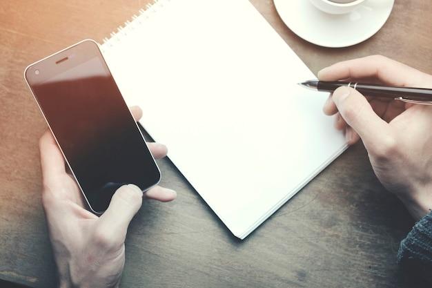 Mężczyzna pracujący - długopis i telefon, filiżanka kawy na drewnianym stole