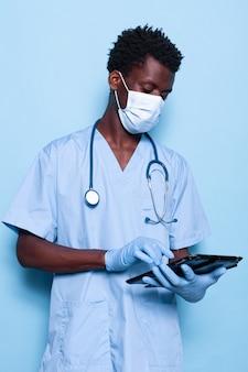 Mężczyzna pracujący jako pielęgniarka trzymający cyfrowy tablet w studio