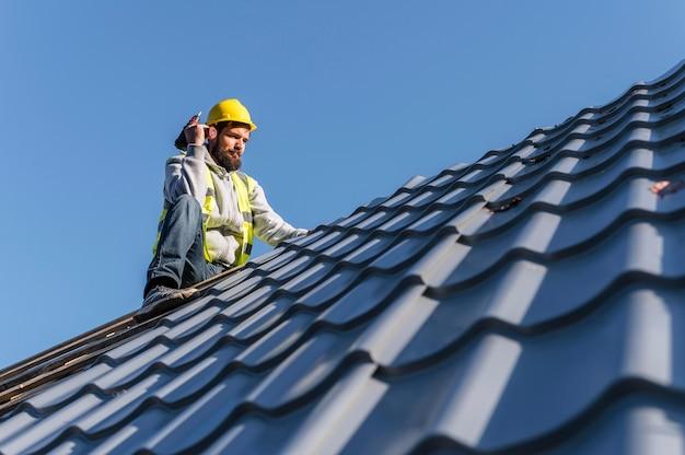Mężczyzna pracujący na dachu z daleka