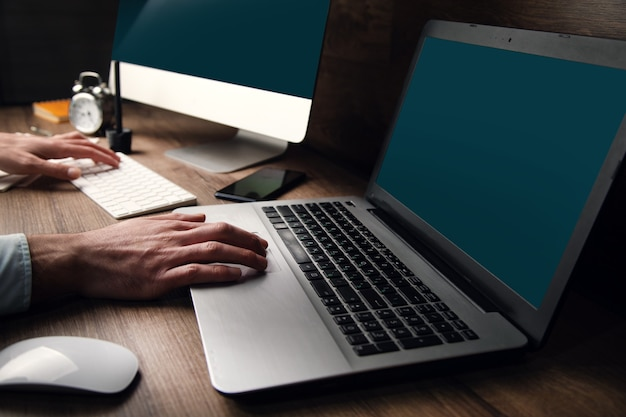 Mężczyzna pracujący na dwóch komputerach w ciemnym biurze