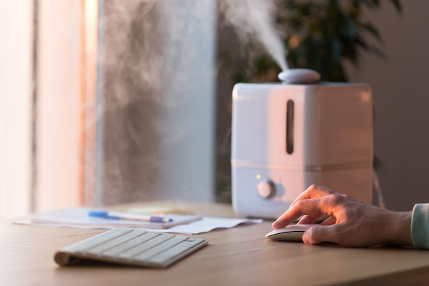Mężczyzna pracujący na komputerze, za pomocą myszy pc w pobliżu dyfuzora olejków aromatycznych na stole, para z nawilżacza powietrza, selektywne ustawianie ostrości