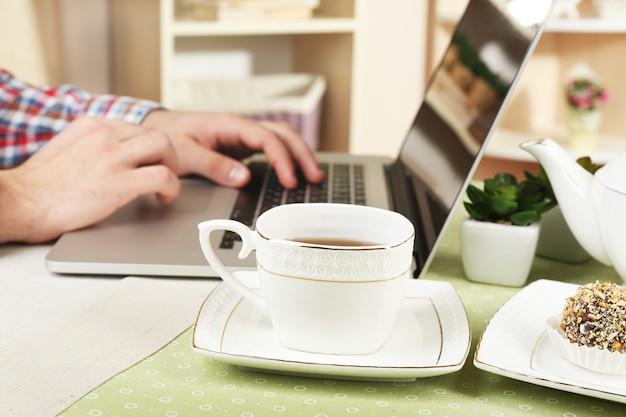 Mężczyzna pracujący na laptopie na drewnianym stole na tle wnętrza domu