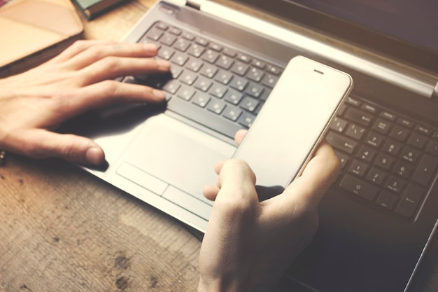 Mężczyzna pracujący na laptopie na drewnianym stole